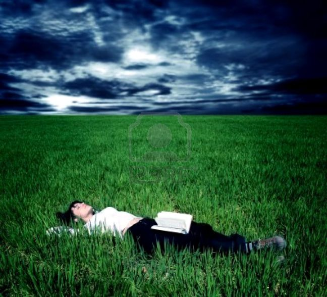 5721887-young-woman-lying-in-a-grass-field-with-a-book-and-a-stormy-sky
